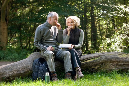 A mature couple sitting on a tree trunk eating a packed lunch : Stock Photo