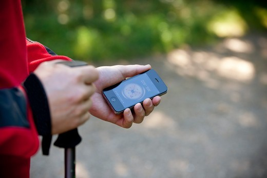 A man holding a smartphone with a compass application, close up : Stock Photo