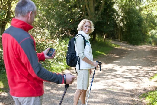 Stock Photo: 1804R-21246 A mature couple walking along a country path, navigating with a smartphone