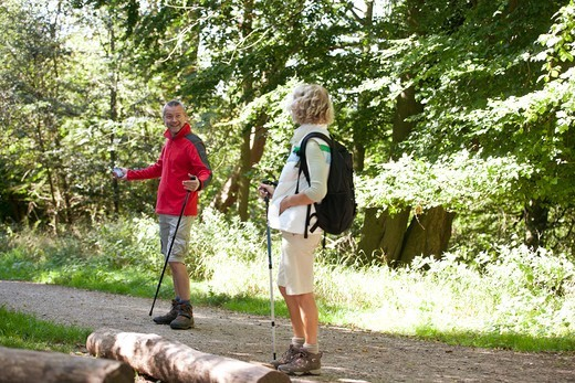 Stock Photo: 1804R-21247 A mature couple walking along a country path, navigating with a smartphone