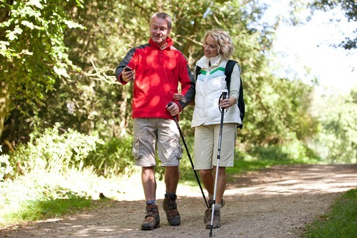 A mature couple walking along a country path, navigating with a smartphone : Stock Photo