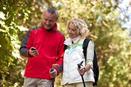 Stock Photo: 1804R-21250 A mature couple walking in the countryside, looking at a smartphone