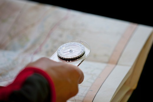 Stock Photo: 1804R-21254 A man holding a map and compass, close up