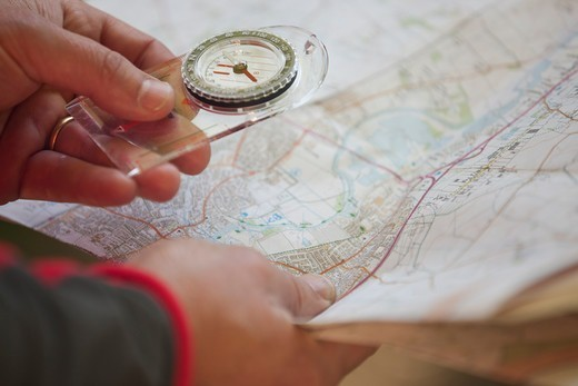 A man holding a map and compass, close up : Stock Photo