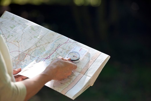Stock Photo: 1804R-21256 A woman holding a map and compass, close up