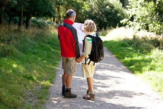 Stock Photo: 1804R-21259 A mature couple walking in the countryside, holding a map