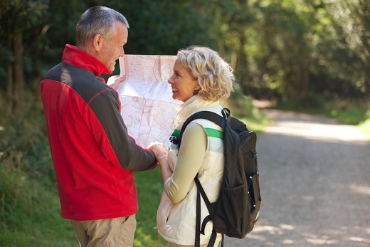 Stock Photo: 1804R-21260 A mature couple walking in the countryside, holding a map