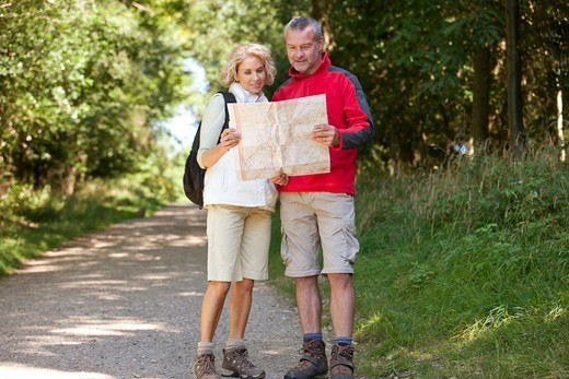 Stock Photo: 1804R-21261 A mature couple walking in the countryside, looking at a map