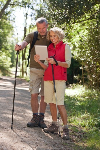 A mature couple out walking on a country path, navigating with a tablet computer : Stock Photo