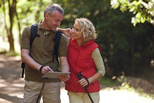 A mature couple out walking on a country path, navigating with an ipad : Stock Photo