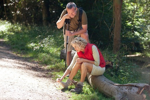 Stock Photo: 1804R-21266 A mature couple resting beside a country path, woman massaging her sore feet