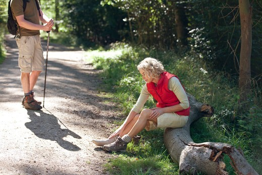 A mature couple resting beside a country path, woman massaging her sore feet : Stock Photo