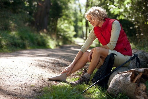 Stock Photo: 1804R-21268 A mature woman resting beside a country path, massaging her sore feet