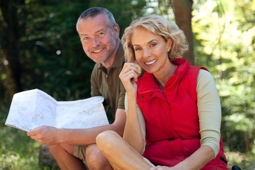 Stock Photo: 1804R-21270 A mature couple sitting outdoors resting, man holding a map