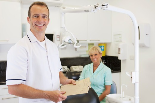 A male dentist and female nurse in a dental surgery : Stock Photo