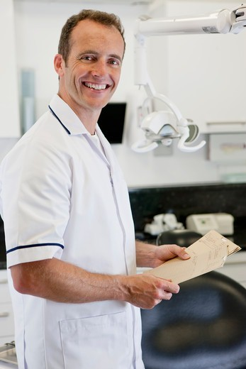 A male dentist holding patient dental records : Stock Photo