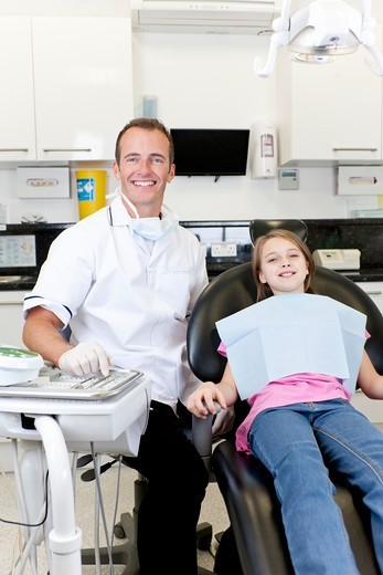 A male dentist with a young girl patient : Stock Photo