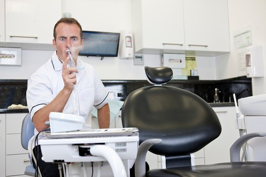 A male dentist in his surgery testing a dental drill : Stock Photo