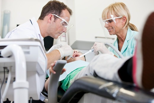 Stock Photo: 1804R-21291 A male dentist and female dental nurse with a young patient