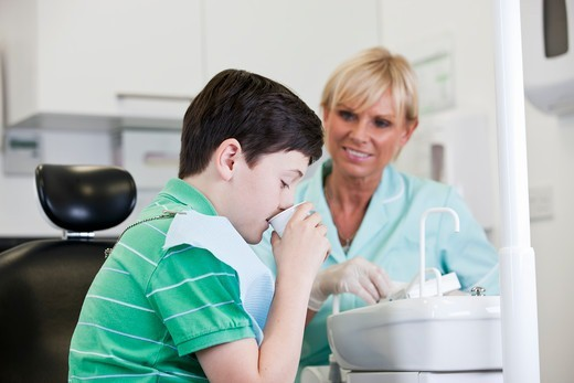 A young boy rinsing his mouth at the dentists, dental nurse/hygienist looking on : Stock Photo