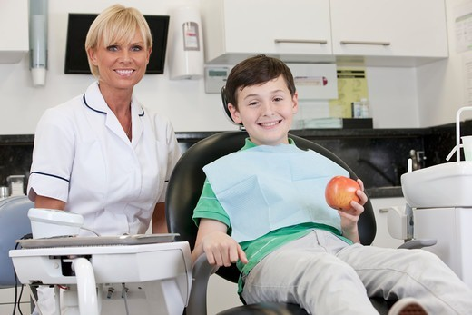 Stock Photo: 1804R-21299 A young boy at the dentist holding an apple