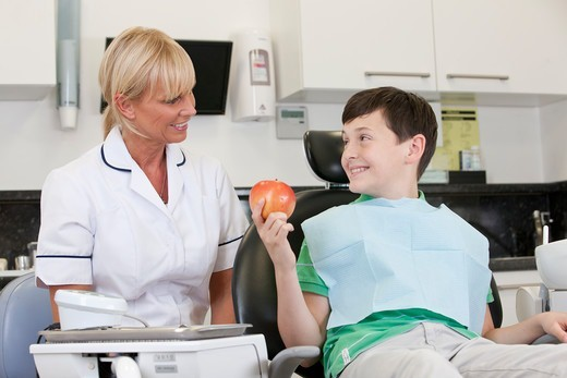 Stock Photo: 1804R-21300 A young boy at the dentist holding an apple