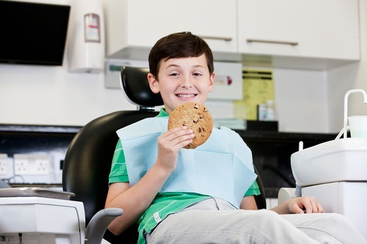 Stock Photo: 1804R-21301 A young boy at the dentist holding a giant cookie