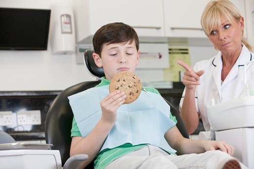 Stock Photo: 1804R-21302 A young boy at the dentist holding a giant cookie, dental nurse/hygienist telling him off