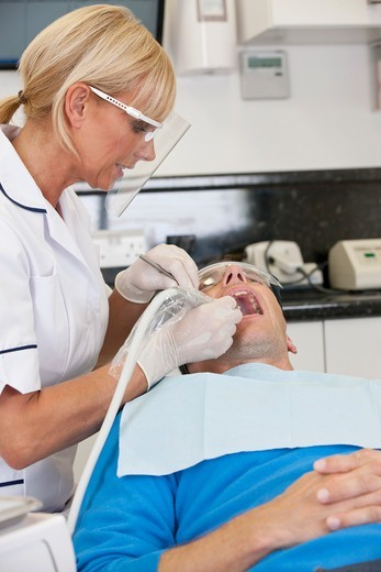 A female dentist treating her male patient : Stock Photo