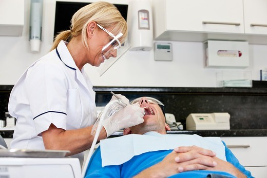 Stock Photo: 1804R-21307 A female dentist treating her male patient