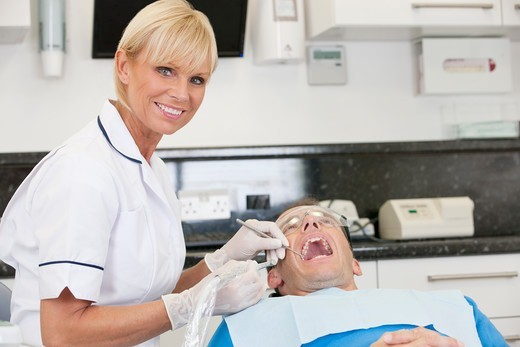 Stock Photo: 1804R-21308 A female dentist treating her male patient