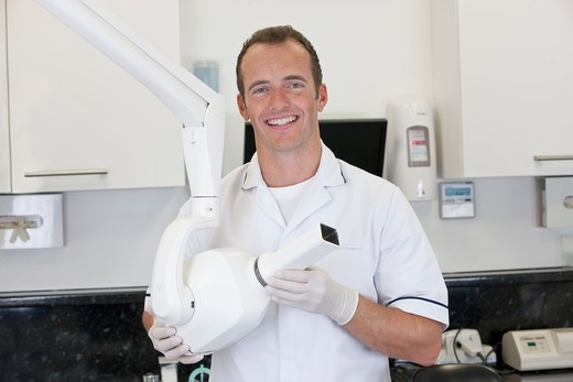 Stock Photo: 1804R-21312 A male dentist holding an x-ray machine