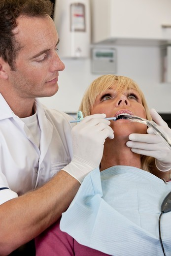 Stock Photo: 1804R-21314 A male dentist inserting a dental x-ray holder in a patient mouth