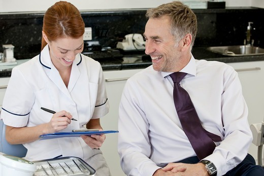 Stock Photo: 1804R-21317 A female dentist discussing dental records with a male patient
