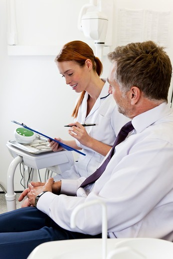 Stock Photo: 1804R-21318 A female dentist discussing dental records with a male patient