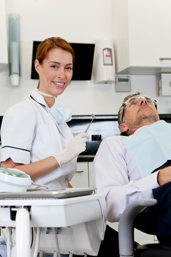Stock Photo: 1804R-21320 A female dentist with a male patient
