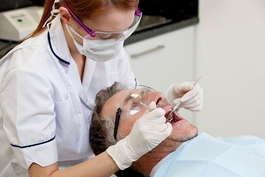 Stock Photo: 1804R-21325 A female dentist examining a male patients teeth, close up