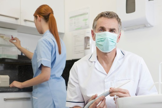 A male dentist and female dental nurse in a dental surgery : Stock Photo