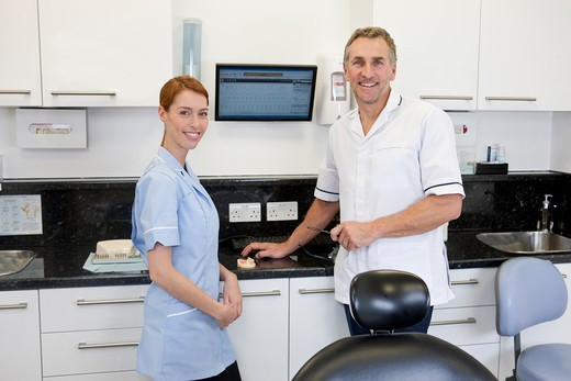 A dentist and dental nurse in a dental surgery : Stock Photo