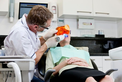 A male dentist filling a female patients teeth : Stock Photo