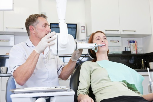 Stock Photo: 1804R-21349 A male dentist taking an x-ray of a female patients teeth