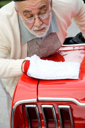 A senior man polishing a sports car : Stock Photo