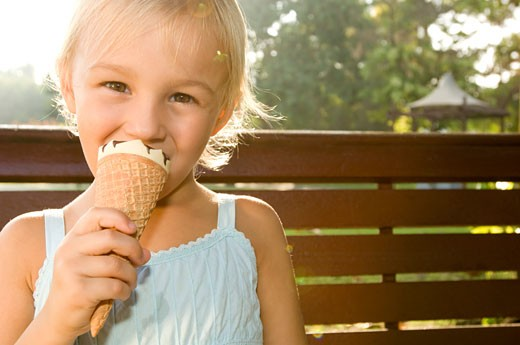 A young girl eating an ice cream : Stock Photo