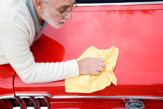A senior man polishing a sports car : Stock Photo