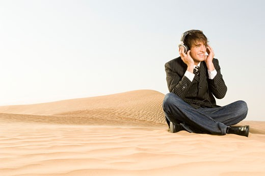 A young man listening to music : Stock Photo