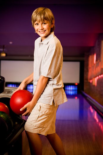 Stock Photo: 1804R-3205 Boy in a bowling alley holding a red bowling ball