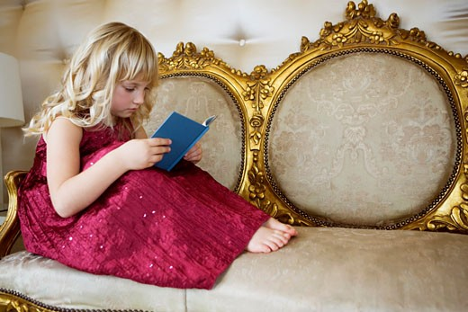 Stock Photo: 1804R-3242 Little girl in a party dress, reading a book
