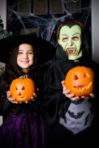 Stock Photo: 1804R-3809 Children in Hallowe'en costumes, holding pumpkins with carved faces