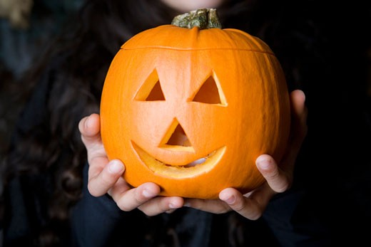 Child holding Hallowe'en pumpkin with a carved face : Stock Photo