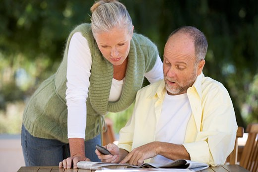 Stock Photo: 1804R-4126 A senior couple discussing an article in a paper